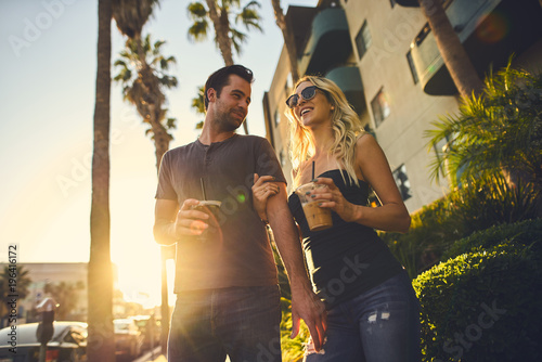 trendy attractive couple walking together with coffee in los angeles