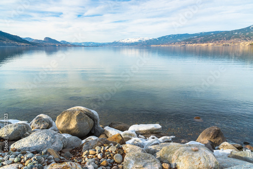 Foto op Aluminium Strand Rocky shoreline in foreground with view of calm lake and snow covered mountains in distance