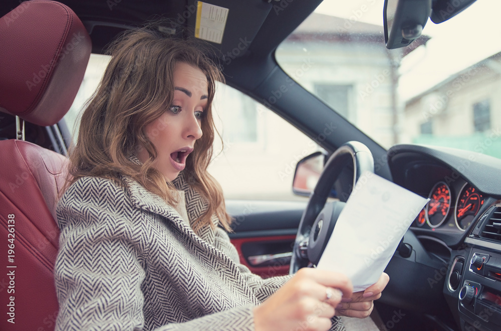 Fototapety, obrazy: Shocked woman in car reading insurance paper