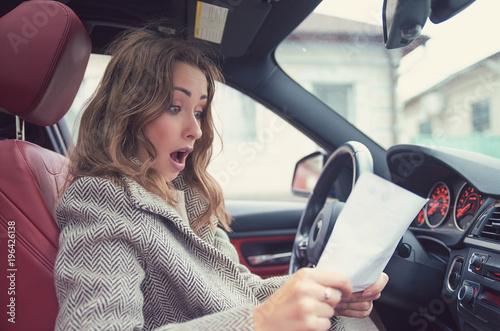 Obraz Shocked woman in car reading insurance paper - fototapety do salonu