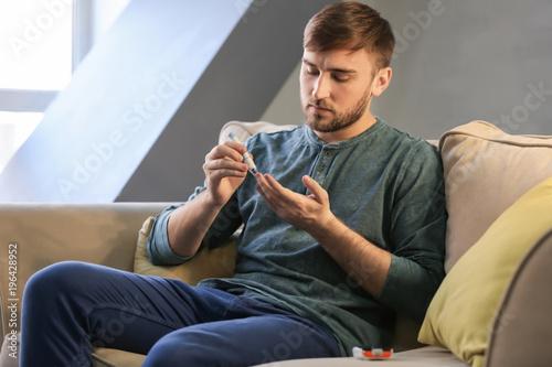 Fotografía  Diabetic man taking blood sample with lancet pen at home