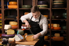 Young Worker Cutting Cheese In...