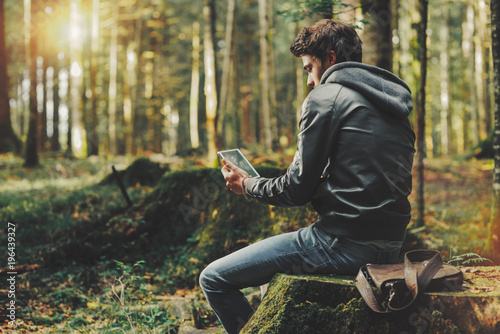 Tuinposter Ontspanning Young man using a digital tablet in the woods