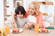 Cute elderly woman helps little boy to cut sausage on plate. Beautiful grandmother helps her grandchild to eat.