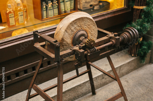 Photo  Ancient stone wheels on wooden structures at the entrance to the store with Christmas decorated showcase