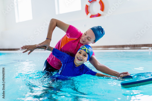 Boy having a swimming lesson with instructor Fototapeta