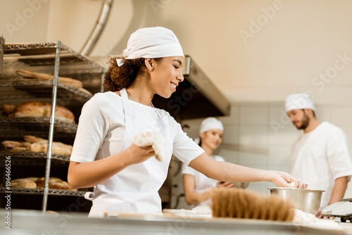 Staande foto Bakkerij multiethnic team of bakers working together at baking manufacture