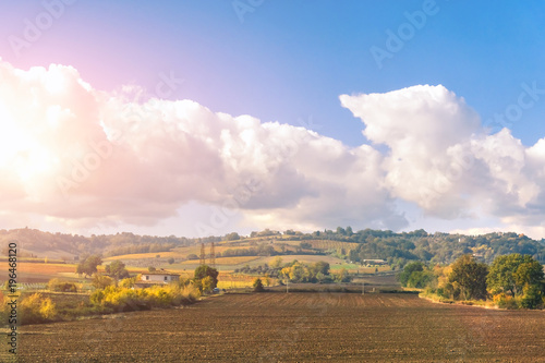 Tuinposter Purper Farmhouses and agricultural field on a sunny day