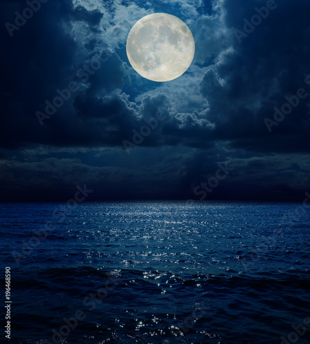 Poster Zee / Oceaan super moon in dark clouds over sea