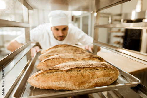 Fotografia young baker putting trays of fresh bread on stand at baking manufacture