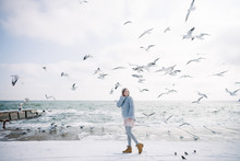 Beautiful Young Girl On Winter Seashore Looking At Seagulls