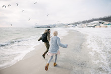 Back View Of Young Couple Holding Hands And Running On Winter Seashore
