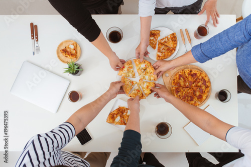 Lunch and people concept. Happy business team eating pizza in office