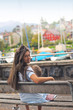 young girl sits on a bench near the pier with yachts and boats in the beautiful spa town of Spiez, Switzerland