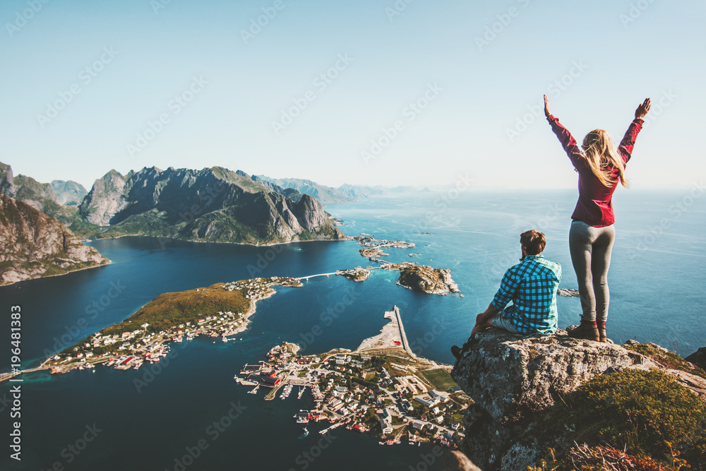 Fototapeta Couple family traveling together on cliff edge in Norway man and woman lifestyle concept summer vacations outdoor aerial view Lofoten islands Reinebringen mountain top