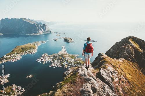 Man traveler hiking on Reinebringen mountain ridge in Norway lifestyle adventure Wallpaper Mural