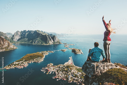 Fototapeta Couple travelers traveling together on top cliff Reinebringen mountain in Norway man and woman family lifestyle concept summer vacations outdoor aerial view Lofoten islands obraz na płótnie