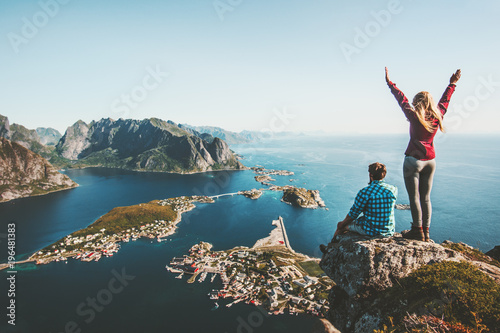 Vászonkép Couple family traveling together on cliff edge in Norway man and woman lifestyle
