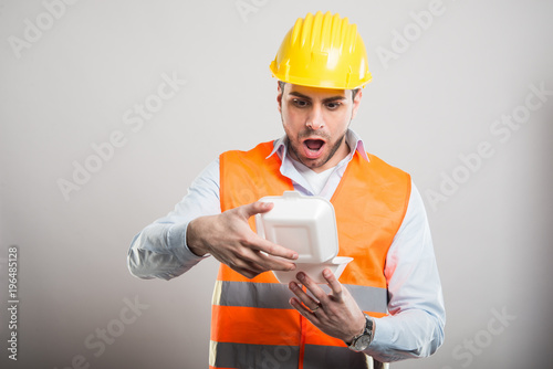 Photo Portrait of architect opening lunch box looking amassed