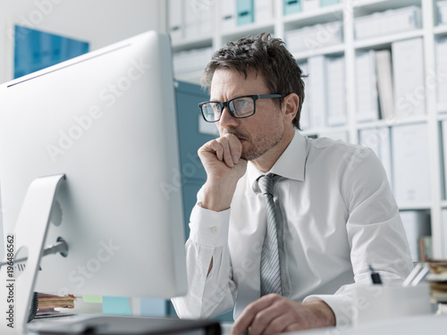 Pensive corporate executive working with a computer