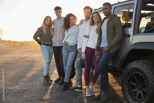Fotomural  Young adult friends on a road trip standing by their jeep