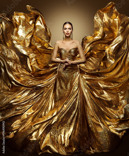 Photo  Gold Woman Flying Dress, Fashion Model in Waving Golden Gown, Fluttering Fabric