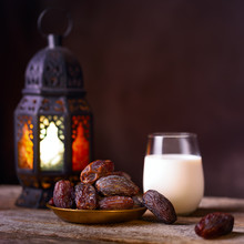 Ramadan Concept. Dates Close-up In The Foreground. Ramadan Lantern And Glass Of Milk On A Wooden Table. Textured Green Wall Background. Space For Text On The Right. Square 1:1 Frame.