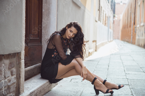 fototapeta na drzwi i meble Travel tourist girl on vacation posing on city street with beautiful legs in high heel shoes. Attractive young romantic passion woman sitting on sidewalk against beautiful view on venetian quiet