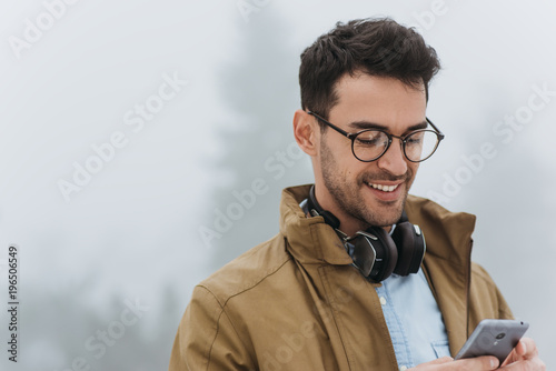 Obraz Happy handsome man looking down, wearing eyeglasses, coat and black headphones to listening the music from smartphone in the misty park outdoor. People, technology and lifestyle concept - fototapety do salonu