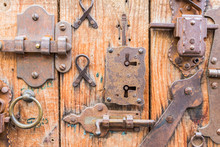 Different Lockers, Knobs And Iron Hinges On Wooden Door..