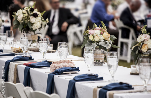 Fototapeta Table set up for wedding reception with people out of focus in background. obraz