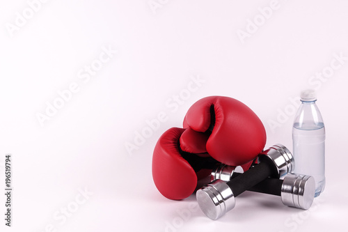 A pair of boxing gloves and dumbbells and a bottle of water. Ready for a hard fight workout. Concepts for martial arts, boxercise, gym and workout, etc. Place for own text / copy space.