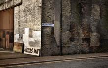 Vintage Look Corner Of Loftie Street In Southwark, London With Dirty Old Brick Wall.
