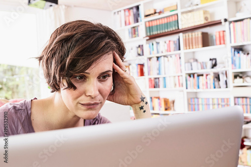 Mid adult woman at home, using laptop, worried expression