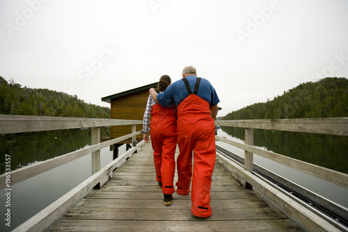 Mature adult man walking down a jetty with his teenage granddaughter while wearing red overalls.