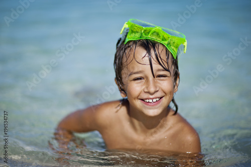 Portrait of a smiling young boy in a swimming pool.