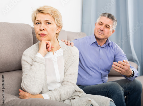 Valokuvatapetti resentful mature couple quarreling at home with each other