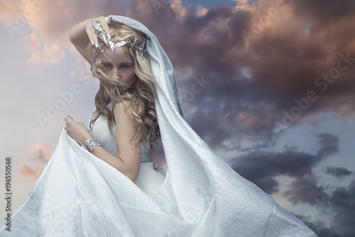 Fotografia Mythology, Greek goddess, blond woman with silver laurel wreath dressed in white silks in the wind