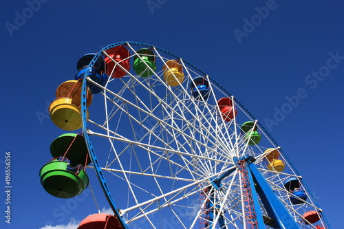 Foto  Colourful Ferris Wheel over the blue clear sky with red, green, blue and yellow