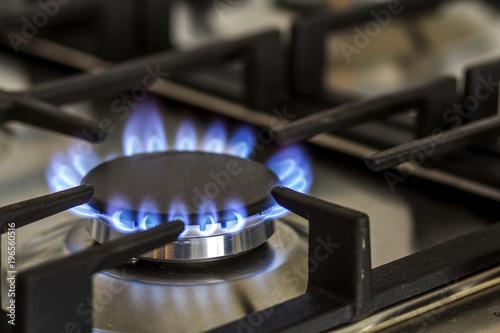 Fotografija Natural gas burning on kitchen gas stove in the dark