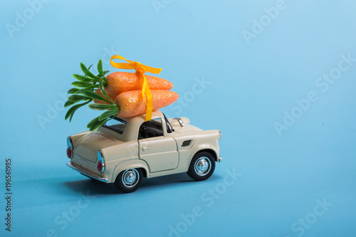 Toy car carrying easter carrots isolated on blue background