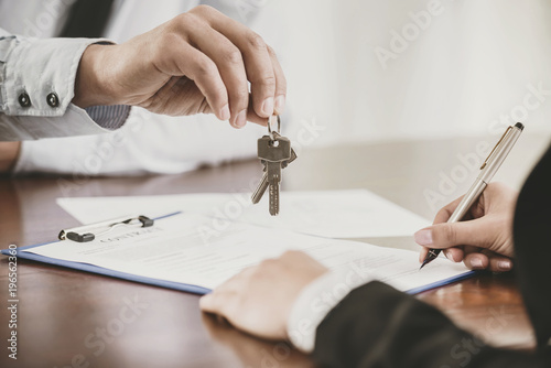 Photo  Young woman is signing financial contract with male realtor
