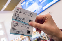 Two Tickets In A Woman's Hand For Travel By High-speed Train CRH