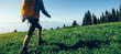 woman hiker walking on beautiful green mountain hill