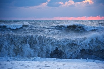 Storm on the sea. Large waves roll on the shore. The sun at sunset makes its way through the clouds.