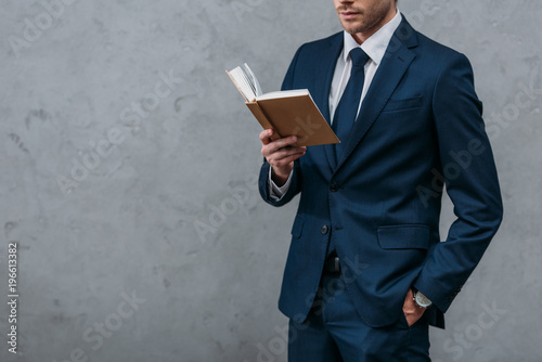 Fotografia  cropped shot of businessman reading book in front of concrete wall