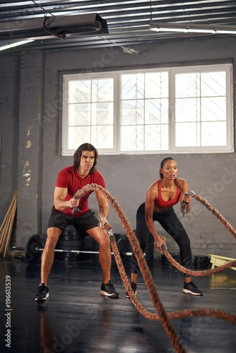 Keuken foto achterwand Ontspanning Man and woman working out with ropes in gym