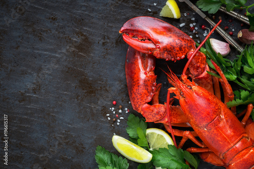 Fototapeta Whole red lobster with fresh parsley, slices of lemon, garlic, salt and pepper beans
