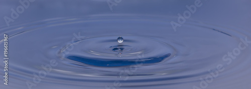 Fototapety, obrazy: drop of water liquid with splash isolated. the drop explodes in the water sending spray to the sides and circle ripples around it. the water is blue