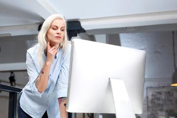 Moda w pracy. Modna młoda kobieta z białymi włosami pracuje przy komputerze w stylowym biurze.